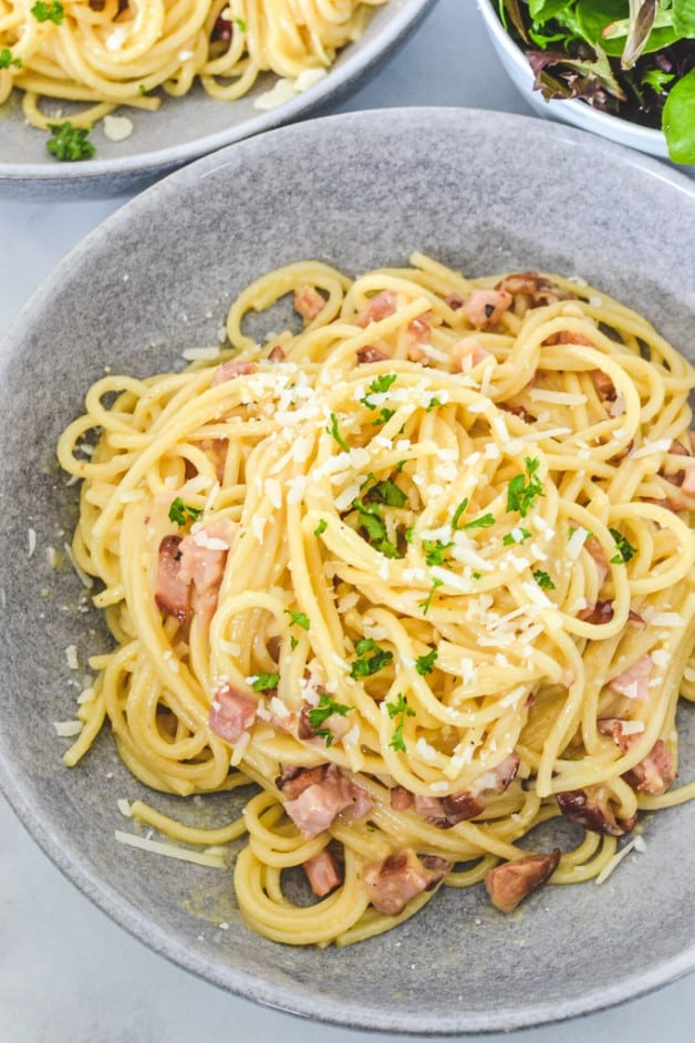 top view of spaghetti carbonara in grey bowls with side salad
