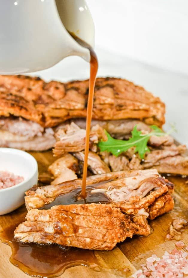 pork belly with crackle on wooden board and white jug pouring brown sauce on top