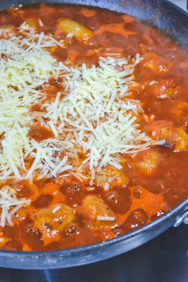 grated cheese melting over red sauce in pan