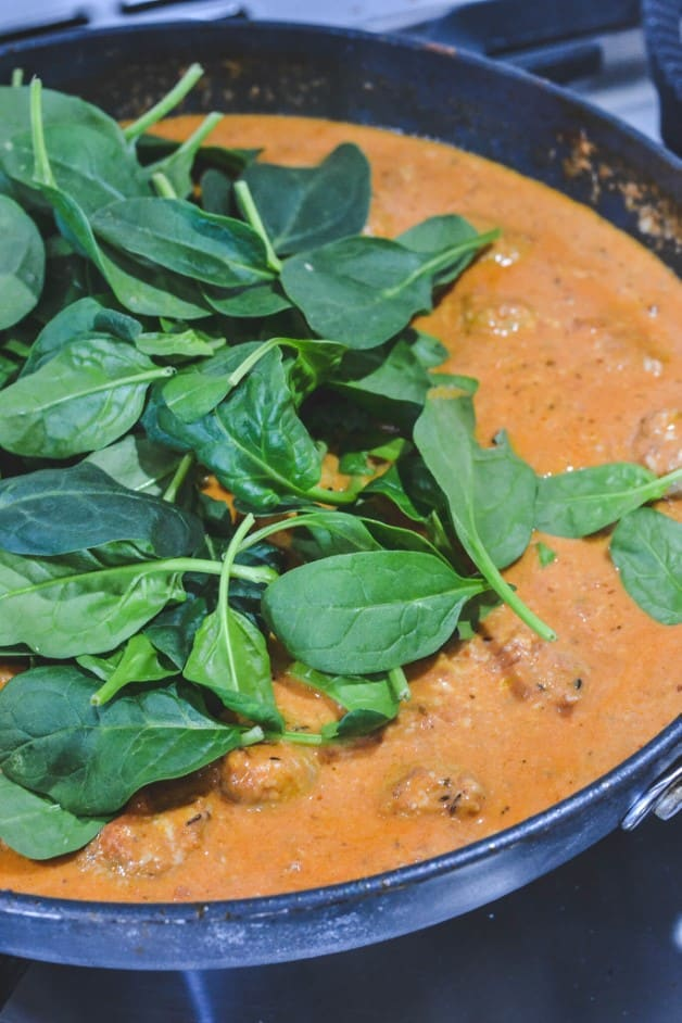 spinach leaves over red sauce in a frying pan