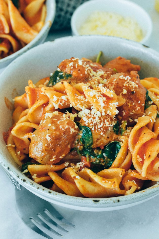 side view of a bowl of pasta with sausage and cheese
