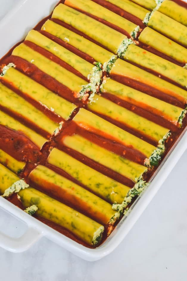 rows of cannelloni tubes arranged over tomato sauce