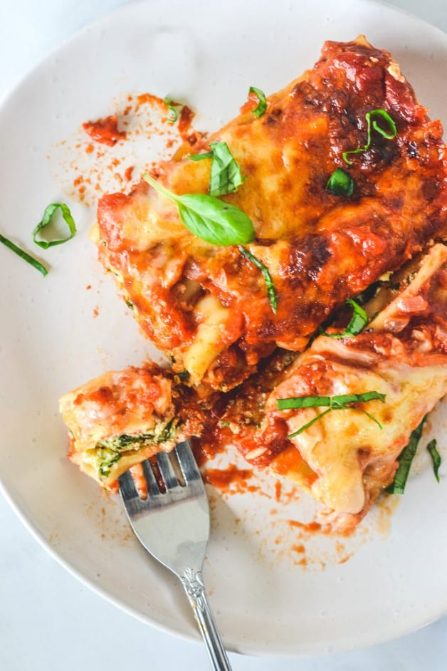 top view of finished cannelloni on a white plate with a fork