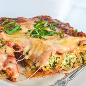 side view of spinach and ricotta cannelloni topped with cheese and basil on white plate