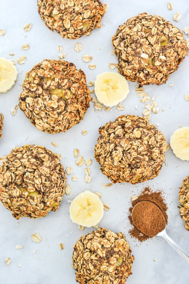 top view of finished cookies with banana pieces, oats and a spoon with cinnamon