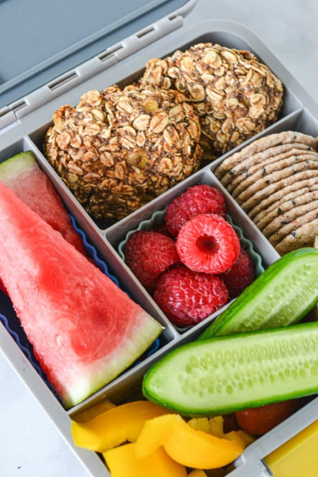 top view of a grey bento box with oat cookies, fruit and other foods