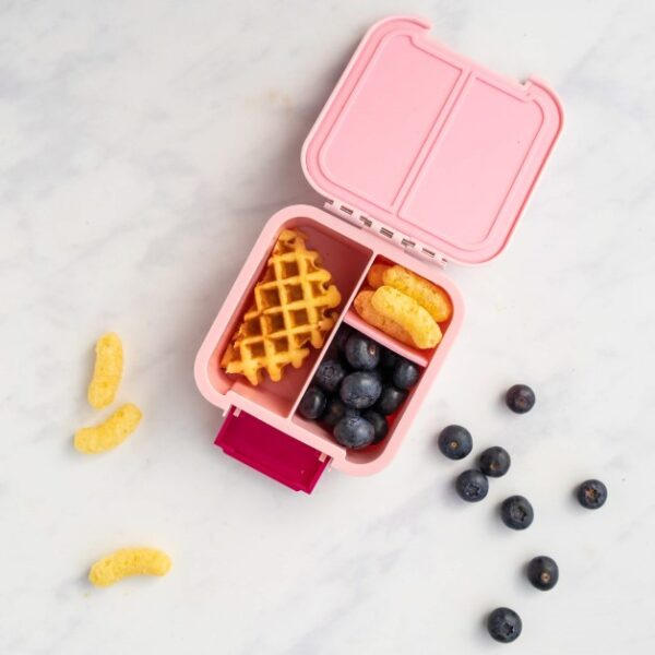 top view of a pink bento lunchbox with fruit
