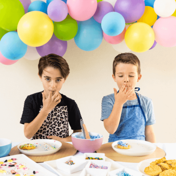 two boys wearing colourful aprons standing at a party table with balloons in background