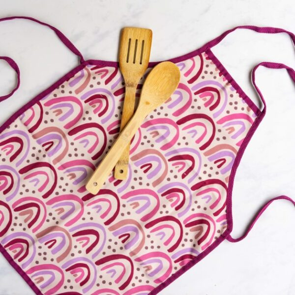 close up of kids apron with rainbow design and wooden spoon