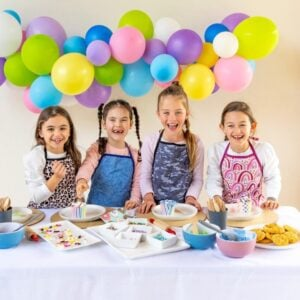 four smiling girls wearing colourful aprons standing at a party table