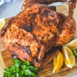 roast chicken on a wooden board with lemon and parsley