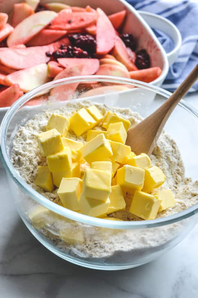 cubes of butter on top of the dry ingredients in a glass bowl