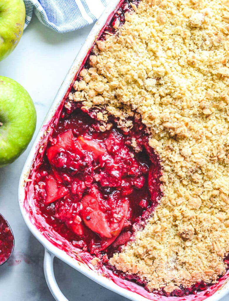 top view of finished crumble in a white baking dish, showing apples and blackberry filling