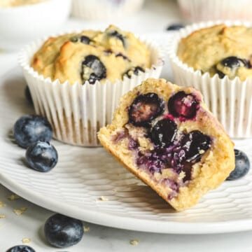 side view of sliced blueberry cupcake on a white plate