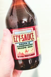 side view of a hand holding a brown bottle labelled 'ezy sauce'