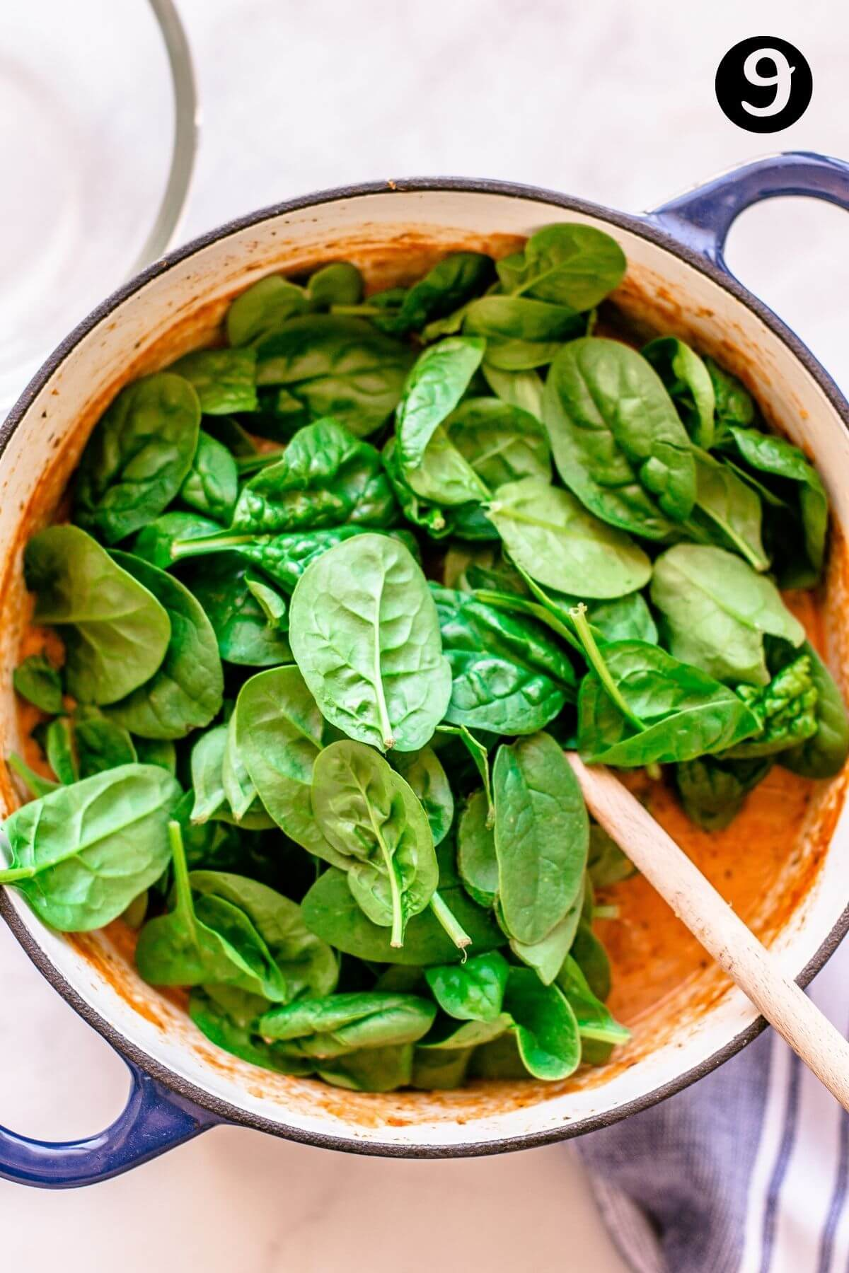 spinach leaves sitting on top of tomato sauce in a pot