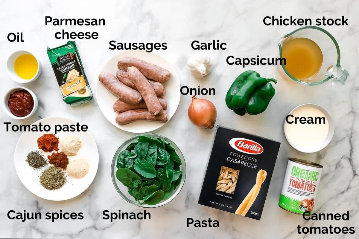 individual ingredients for cajun sausage pasta laid out on a table