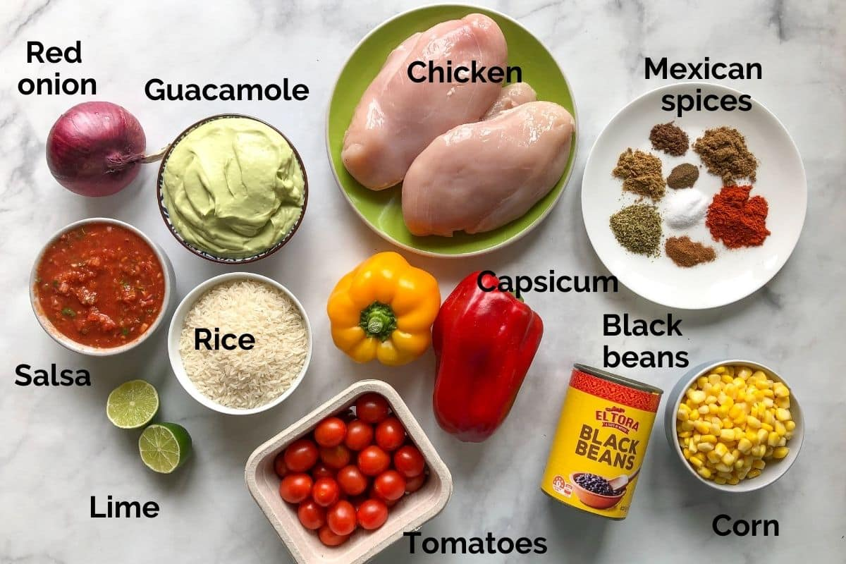 individual ingredients for chicken burrito bowls laid out on a table
