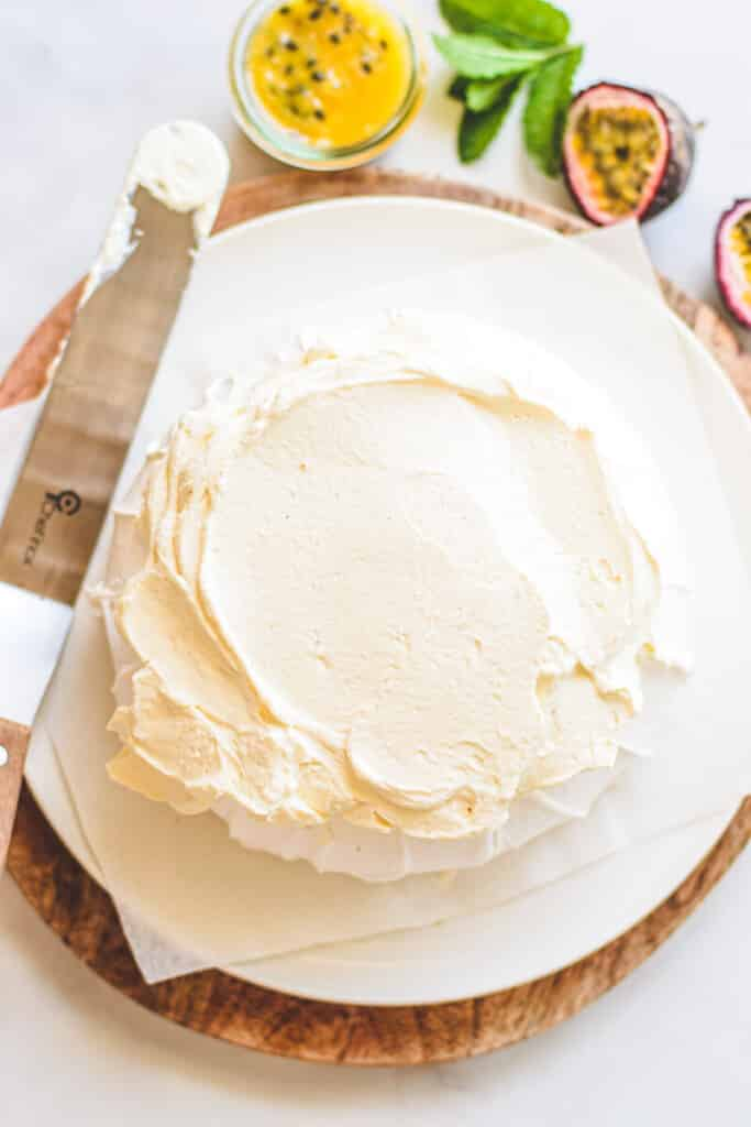 top view of plate with pavlova topped with whipped cream, with a spatula to the side