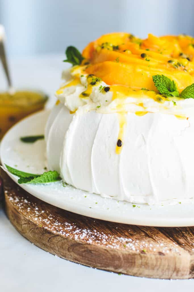 side view of pavlova and mango on a white plate