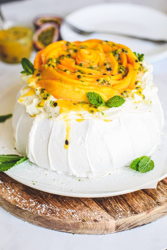 side view of finished pavlova on a wooden board with mango