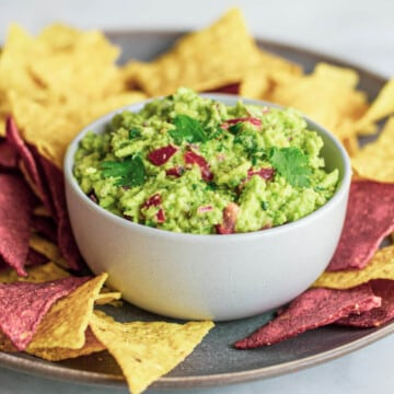 guacamole in a white bowl, surrounded by yellow and purple corn chips