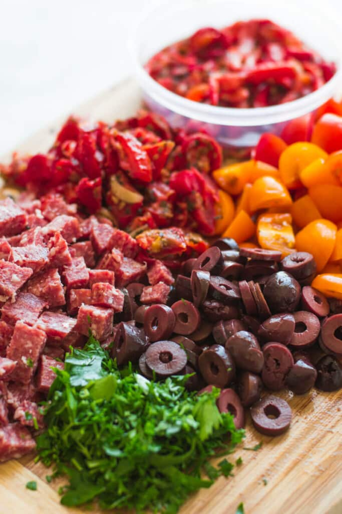 chopped antipasto ingredients on a wooden board
