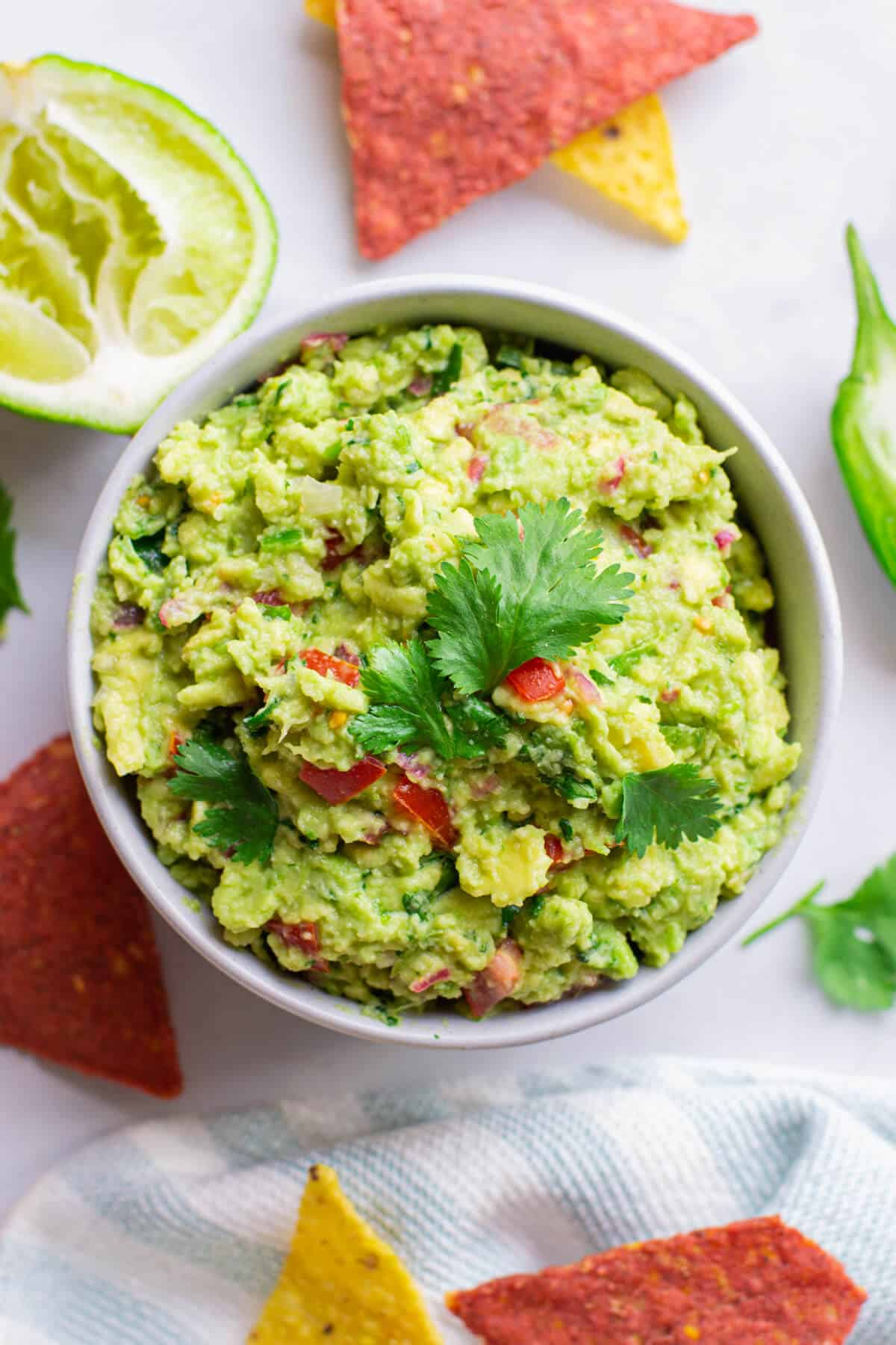 top view of guacamole in a white bowl with corn chips and lime on a table
