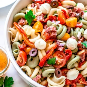 side view of white bowl containing finished pasta salad with pieces of salami and tomatoes