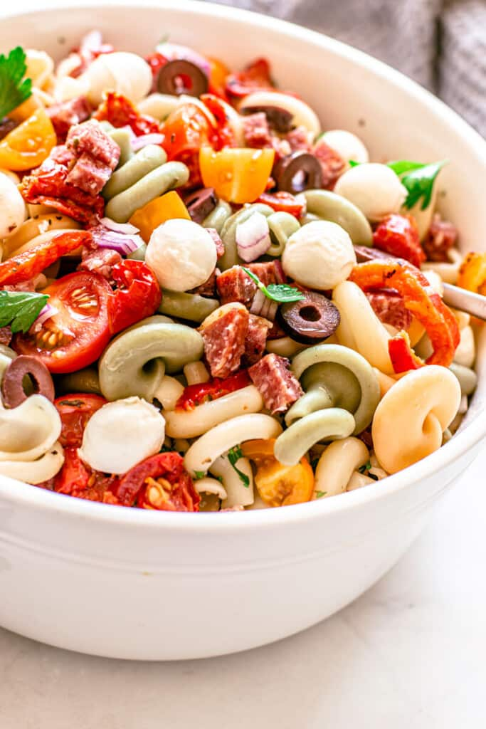 white bowl containing finished pasta salad topped with olives and salami