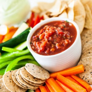 close up of a white bowl with salsa, surrounded by sliced vegetables and crackers