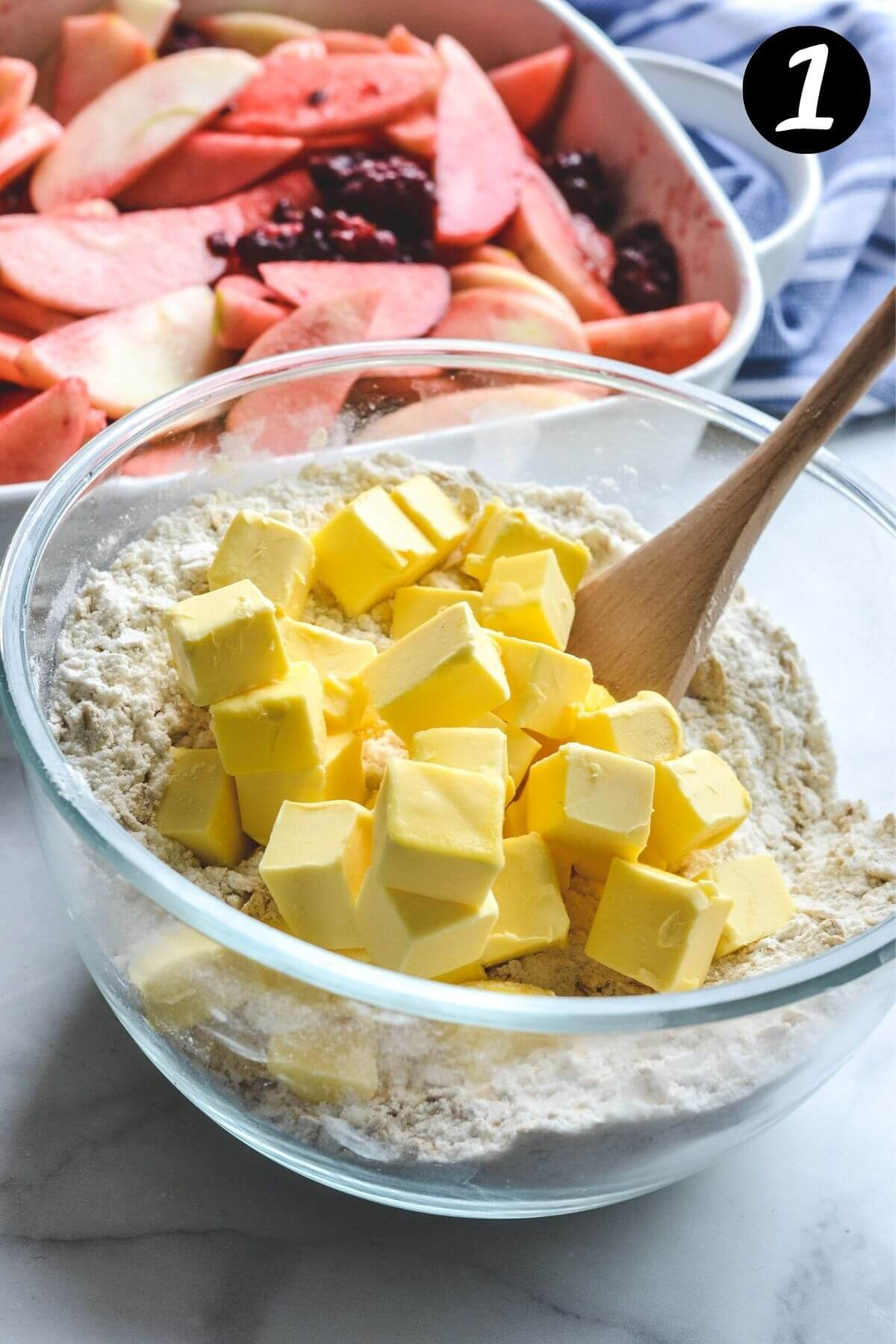 a glass bowl containing crumble ingredients and cubed butter with a wooden spoon