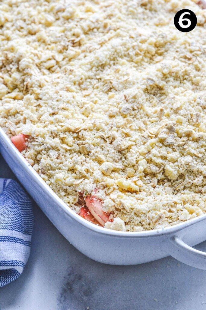 close up of a crumble mixture on top of apples in a baking dish