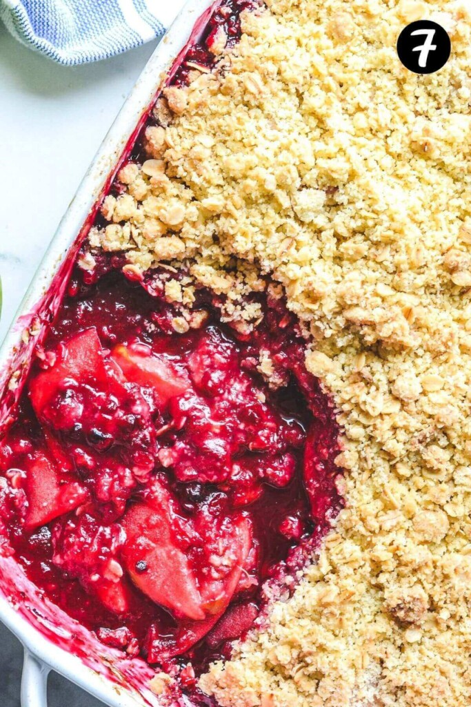top view of a finished apple blackberry crumble in a dish with some crumble removed from the top