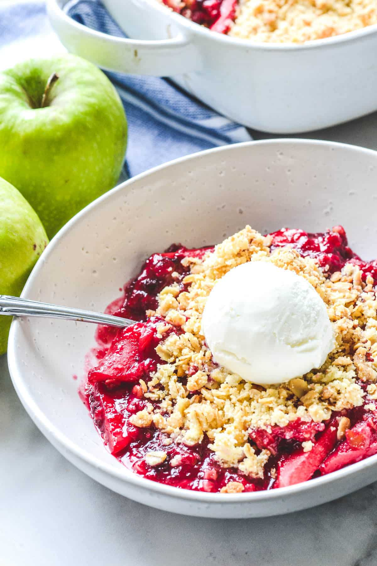 a white bowl containing apple and blackberry crumble and a scoop of ice cream with apples in the background