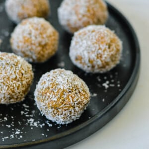 caramel bliss balls on a black plate
