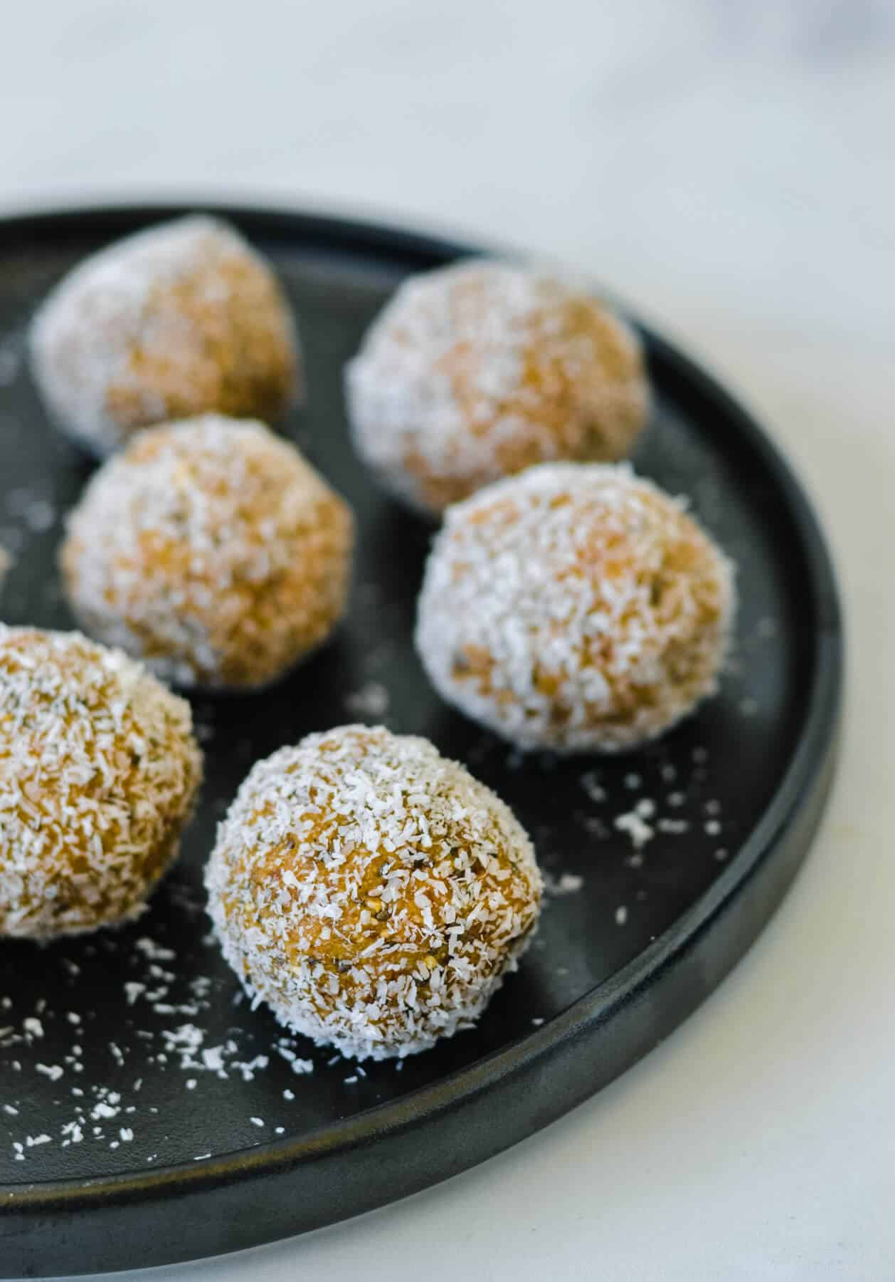 black plate with caramel bliss balls coated in coconut