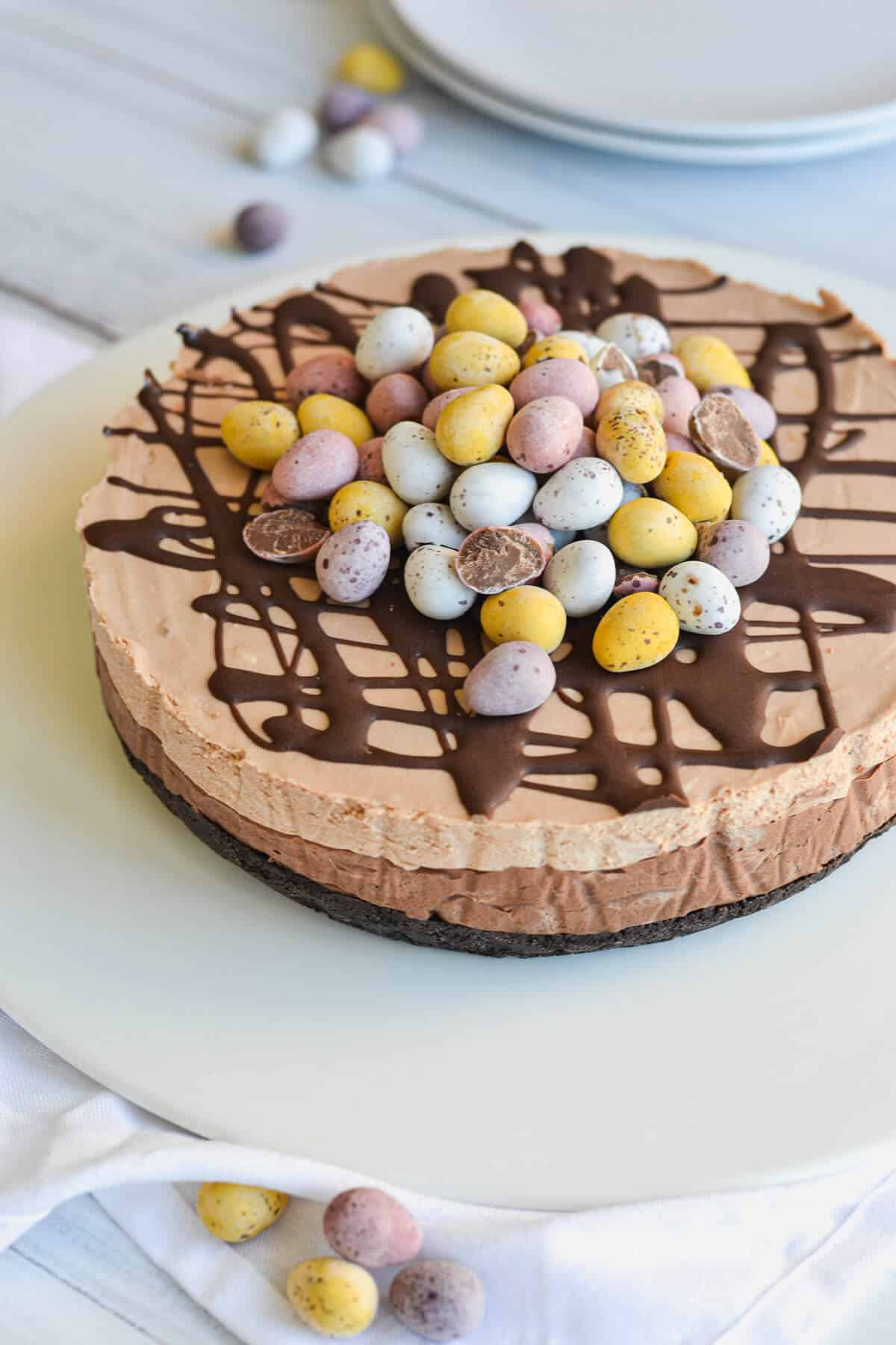 side view of a whole cheesecake topped with melted chocolate and easter eggs