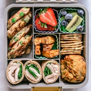 top view of a grey bento lunchbox containing healthy foods