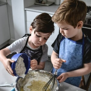 two boys in aprons standing in a kitchen and cooking