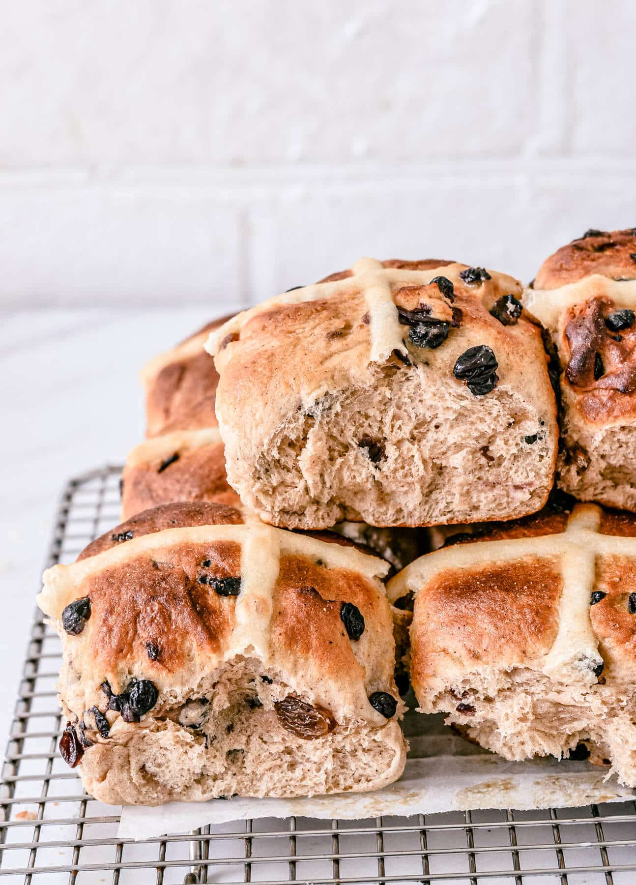 side view of finished hot cross buns cooling on a wire rack