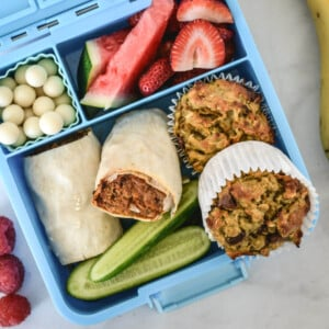 top view of a blue bento lunchbox containing muffins and healthy foods