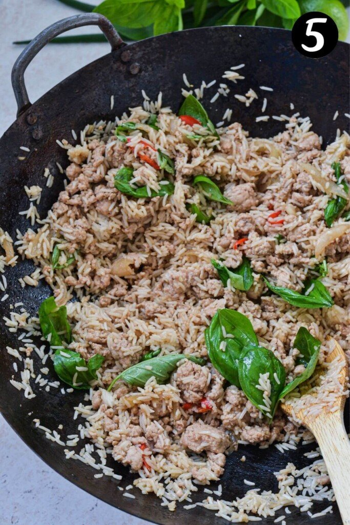 Finished rice with Thai basil frying in a wok