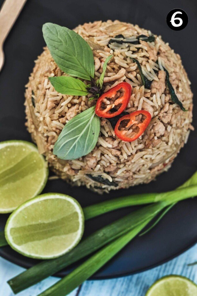 finished fried rice on a black plate with spring onion and lime