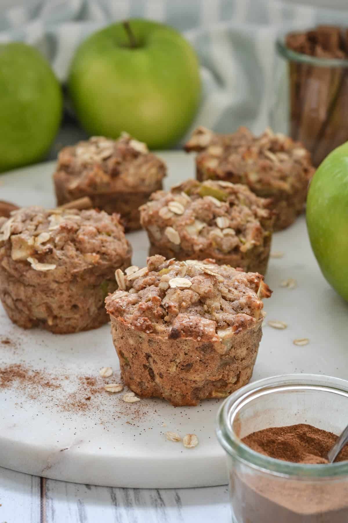 muffins displayed on a white plate with apples and cinnamon sticks