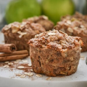 close up of an apple muffin on a white plate with cinnamon sticks
