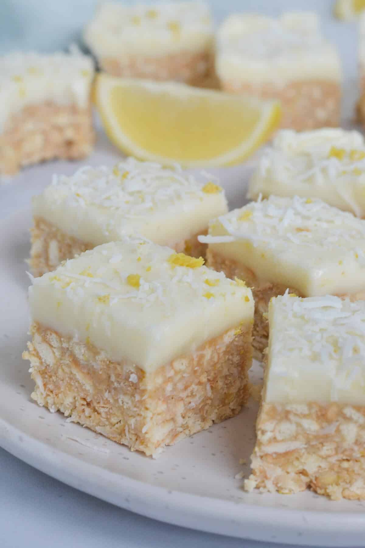 pieces of lemon and coconut slice on a white plate topped with shredded coconut