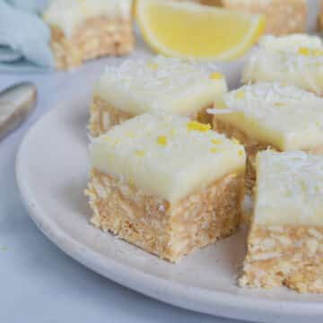 pieces of lemon coconut slice arranged on a white plate