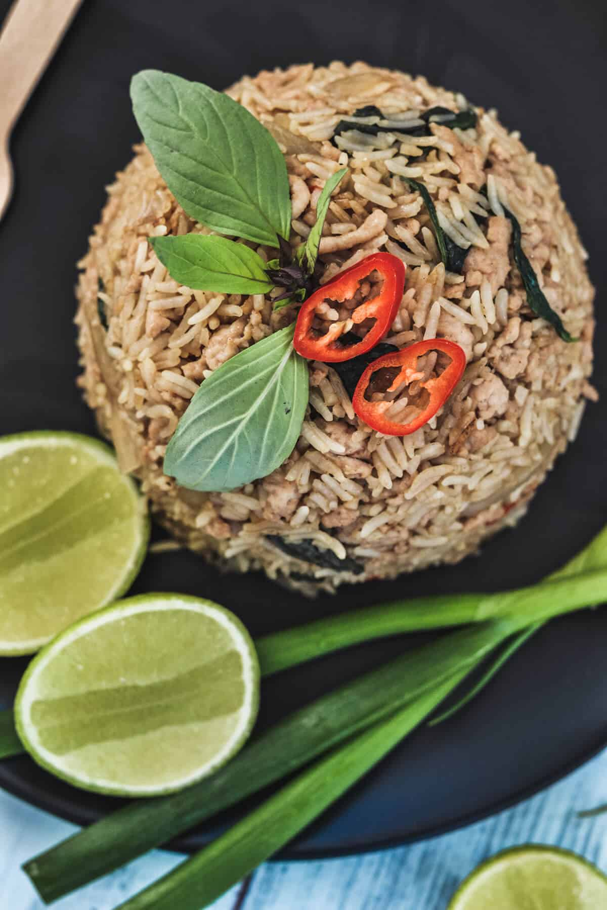 top view of fried rice on a black plate with spring onion, lime and Thai basil