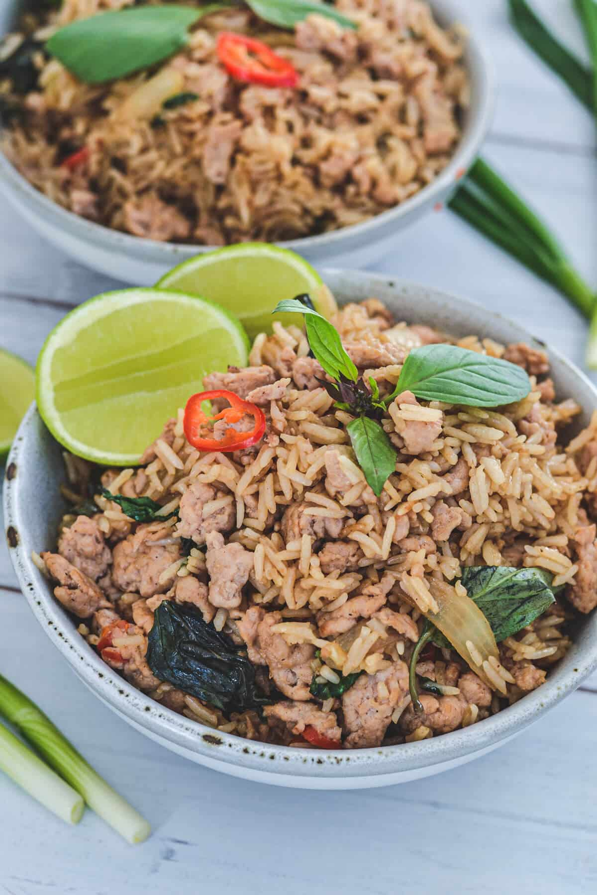 rice in a grey bowl topped with lime, chillies and Thai basil